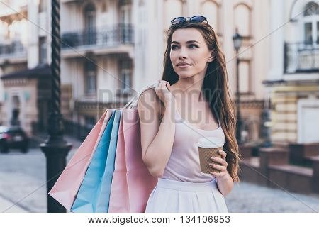 Enjoying coffee after day shopping. Beautiful young woman carrying shopping bags and holding coffee cup while walking along the street