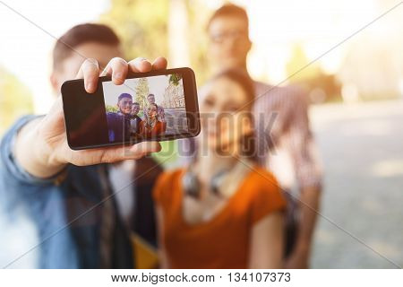 Cheerful young friends are making selfie together. They are standing and laughing. Focus on mobile phone