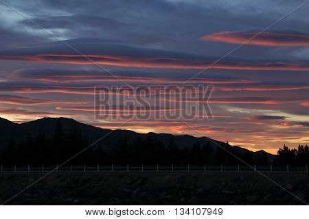 Sunrise in Hawea New Zealand. Colorful clouds over a mountain range.