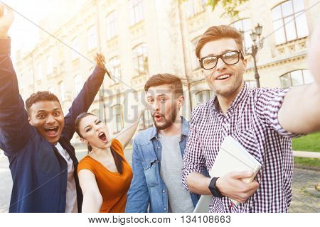 Happy students are celebrating their success. They are making selfie and laughing. The man and woman are standing near a university