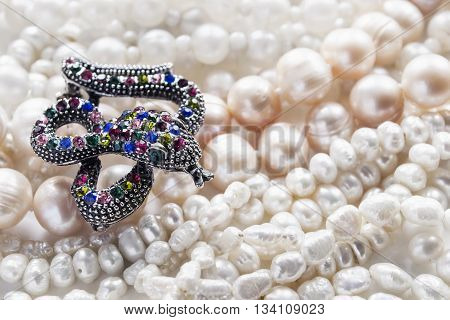 Brooch in the shape of snake on strings of pearl as a background