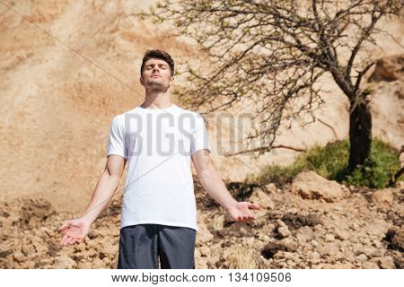 Relaxed handsome young man standing and meditating outdoors