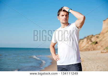 Closeup of attractive young man in white t-shirt standing and thinking on the beach