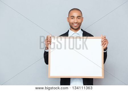 Portrait of smiling african young man holding whiteboard