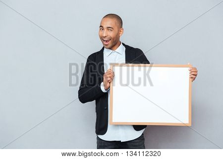 Smiling african american young man winking and holding whiteboard