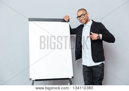 Happy african young man in glasses standing and pointing on blank flipchart
