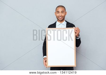 Cheerful attractive african man standing and holding whiteboard