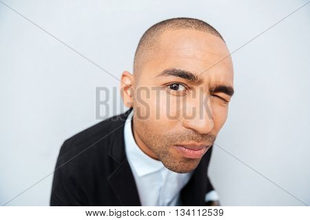Portrait of suspicious funny african american young man closed one eye and looking at camera