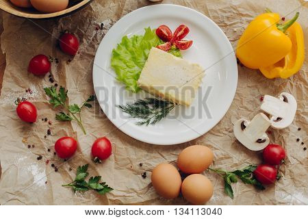 Omelet with ham on parchment background. Vegetable composition