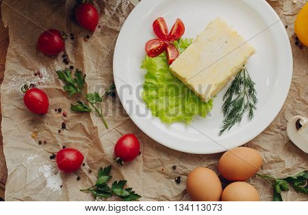 Omelet with ham on parchment background. Vegetable composition. Flat lay.