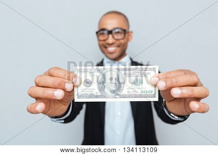 Smiling african american young man in glasses showing dollar banknote