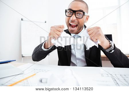 Angry businessman tearing up a document, contract or agreement in office