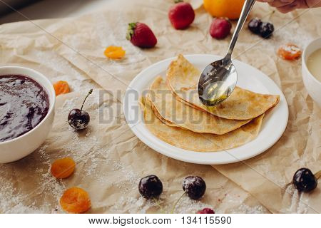 Pancakes and spoon with honey on parchment background.