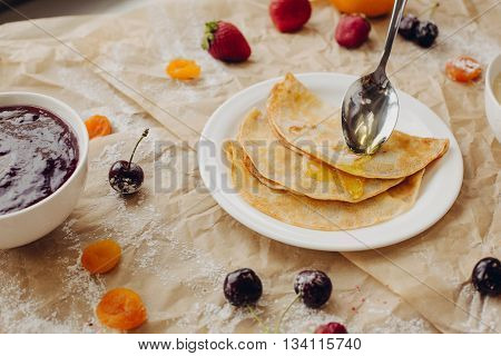 Pancakes and spoon with honey on parchment background