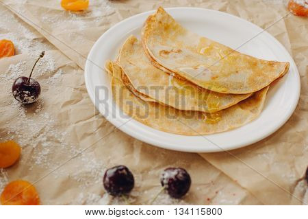Pancakes with jam and berries on parchment background.