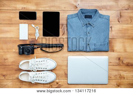 Travel concept shoes, shirt, mobile phone, laptop,mp3, usb, camera, tablet on the desk
