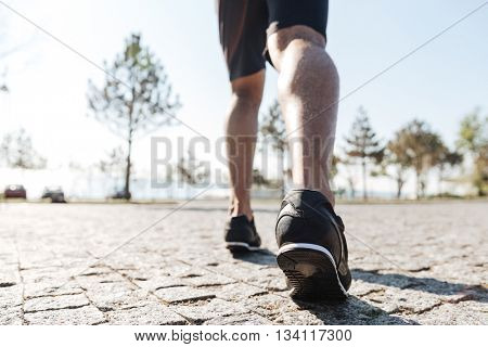 Back view of legs of male sportsman running in the city
