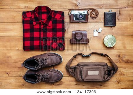 Travel concept boots, shirt, camera, lighter, flask, bag, tin on the desk
