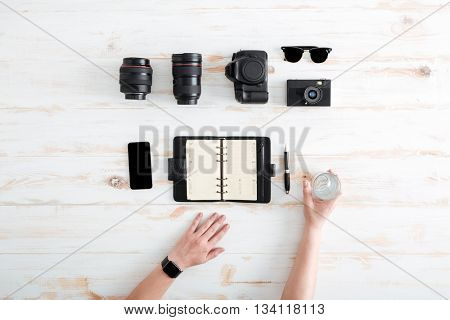 Hands of young man writing in notebook and drinking water on wooden table with blank screen mobile phone, sunglasses, lenses and photo camera