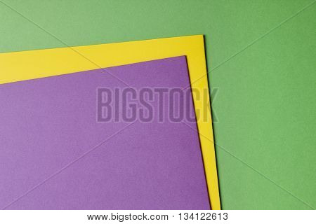 Colored cardboards background in green yellow purple tone. Copy space. Horizontal