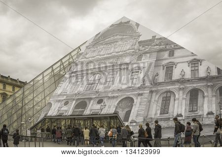 paris, france - may 18, 2016: tourists queued at the louvre pyramid to purchase tickets to the louvre museum. tourism in paris has not suffered as a result of the 2015 terrorist attacks.
