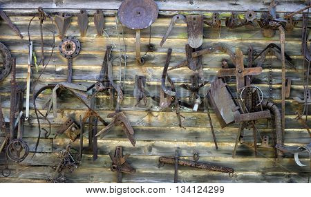 Wall filled with old rusty farm tools and parts hanging on wall