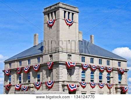 Red white and blue buntings blown by the breeze festoon a building in celebration of America. Sault Ste. Marie Michigan.