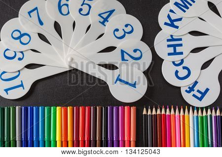 Back to school background with a lot of colorful felt-tip pens and colorful pencils and cards of numerals from one to ten and consonant letters of alphabet on the black school chalkboard