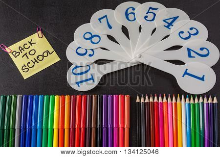 Back to school background with a lot of colorful felt-tip pens and colorful pencils cards of numerals from one to ten and title