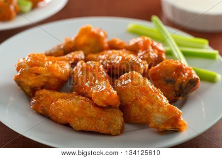 A plate of delicious spicy hot chicken wings with sriracha sauce and celery sticks.