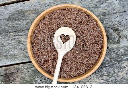 Flax seeds in bamboo bowl with heart wooden spoon