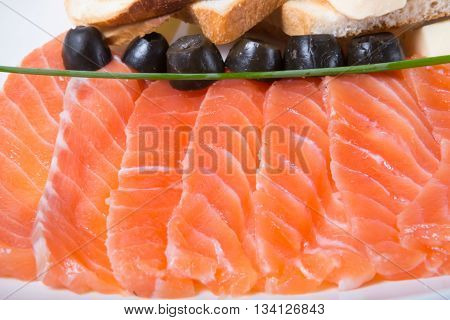 Fresh pink smoked and sliced salmon with croutons