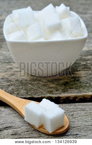 Sugar white cubes in ceramic bowl on rustic table