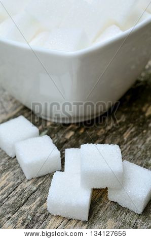 Sugar white cubes in bowl on wooden table