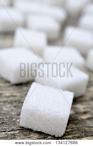 Group of sugar white cubes on rustic table