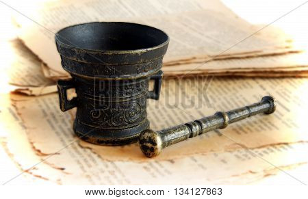 Old bronze mortar and pestle on the pages of ancient book with effect of shallow depth of field and vignette