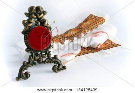 An antique red pincushion in a bronze frame with angels against the background of embroidery with vignetting effect