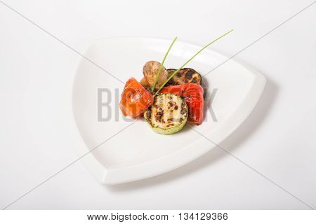 Grilled oily vegetables served on a white plate