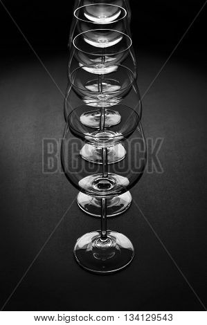 Wine glasses standing in row, empty glasswares with light pattern isolated on dark grey background, selective focus