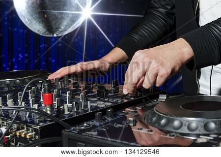 DJ at nightclub party playing on sound mixer, striped blue interior and silver disco ball with star on background, nightlife entertainment industry