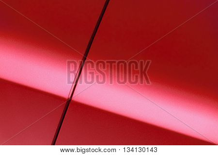 Surface of red sport sedan car, detail of metal fender and door of vehicle bodywork