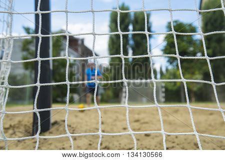 Beach soccer player through the net. Games in Rio.
