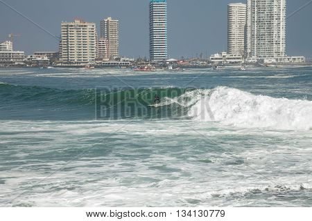 IQUIQUE, CHILE - JULY 28 2013: Man surfing on a wave in Iquique Chile with view of city in background.