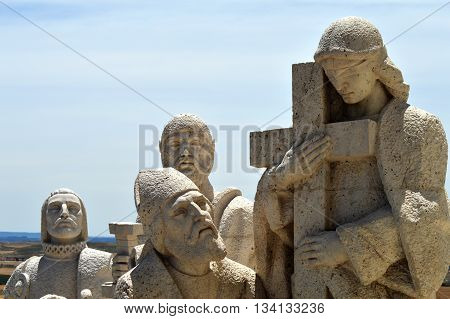 Beautiful group of stone people with a cross
