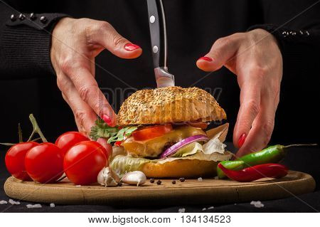 Homemade delicious juicy burger. The girl is going to eat the burger. Burger with women's hands on a dark background.