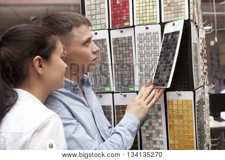 Young happy family couple having fun in store choosing for buying ceramic mosaic looking at design image