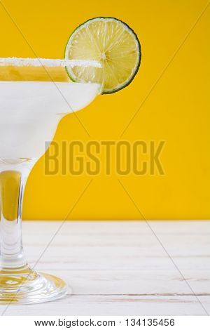 Margarita cocktail on white wooden table and orange background