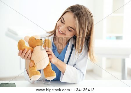 Young beautiful female doctor with toy bear at the office