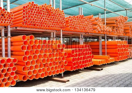 Stack of orange pvc water pipes in abandoned industrial area - Construction concept with plastic equipment pile at building site