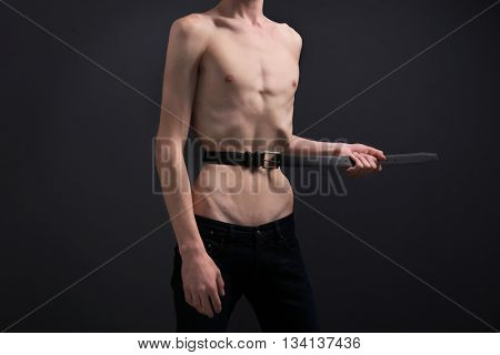 Young man tightening his waist with belt on dark background